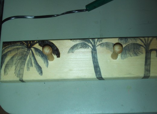Here is what the coat rack looks like with the one palm tree I have begun to woodburn on.