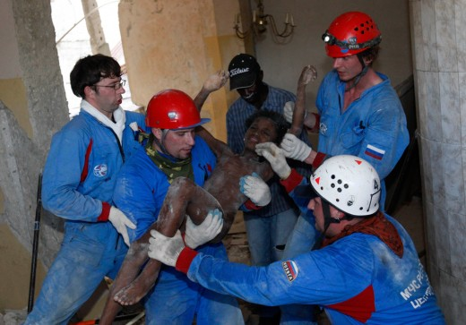Russian rescuers carry Senvilo Ovri, 11, a survivor of the earthquake, out of the remains of a house in Port-au-Prince