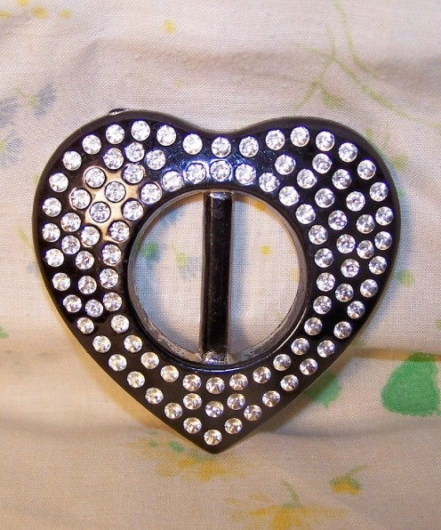 Black plastic heart slide. No rhinestones-circular indentions on front are painted with silver metallic paint.