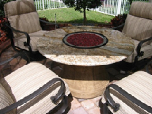 Fire pit table with crushed red glass is a great alternative to an outdoor dining table.  Center hole for fire pit can also hold a grill, ice bin and comes with the granite insert to fill the opening and make the table complete.