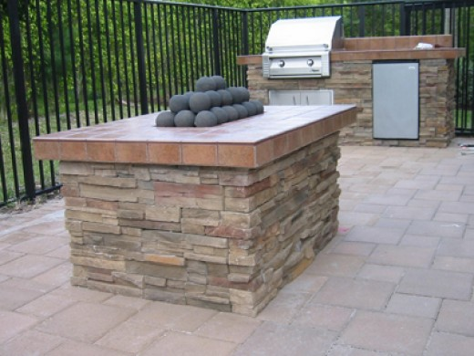 Gas fire pit with cannonballs built to match a small grill island.