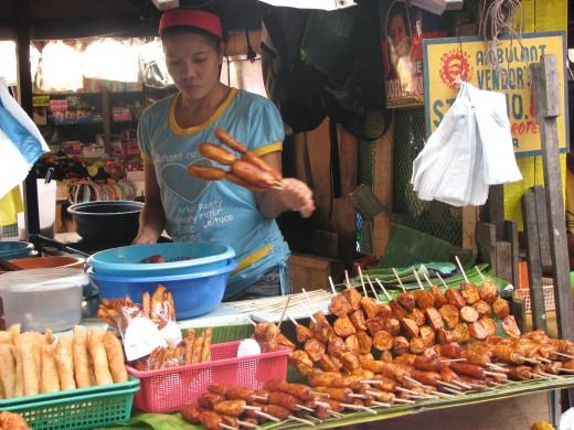 A vendor selling fried banana-que, camote-que as in BBQ also in the lower left there is Turon - bananas wrapped in lumpia wrapper then fried.