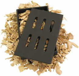 Cast iron wood smoker sits under the cooking grates and adds a wood burning smokey flavor to grilled cooking.