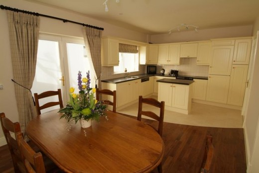 creams and browns delineate areas into kitchen and dining, creating 2 rooms in one space