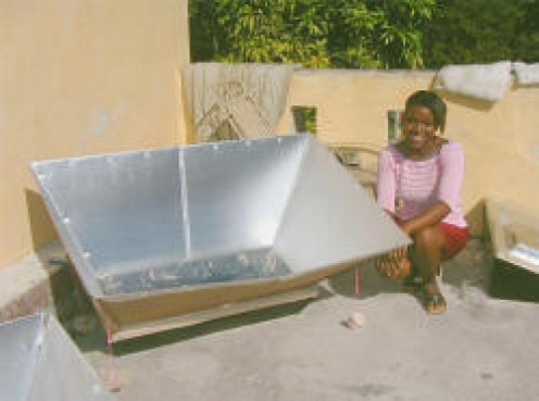 A woman in Haiti tests a solar oven which cooks food, pasteurizes water, and eliminates the need for charcoal, about 55% of a family's income. Haiti has only 2% of its original forests remaining--the rest of the land is bare and subject to erosion.
