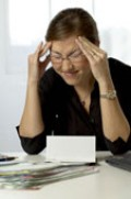 An Asian woman with headache paying bills