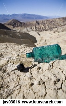 Empty water bottle in desert
