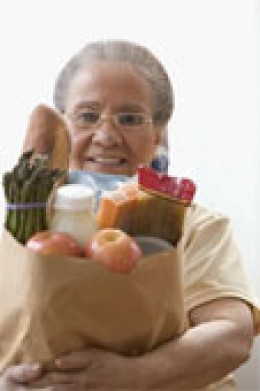 Portrait of a senior woman holding fruits and vegetables in a paper bag