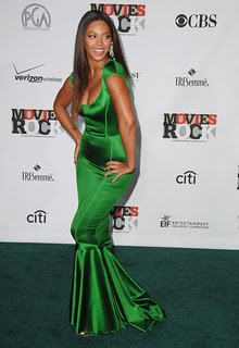 I love this emerald green color. It just makes the dress. Her large silver diamond earrings go perfectly.