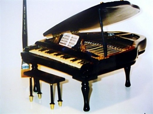 An open grand piano with wires and intricate details, all made out of self hardening clays.