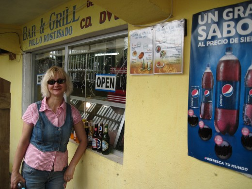 Bella in front of entrance to Bar & Grill On The Spot Restaurant in Coxen Hole, Honduras