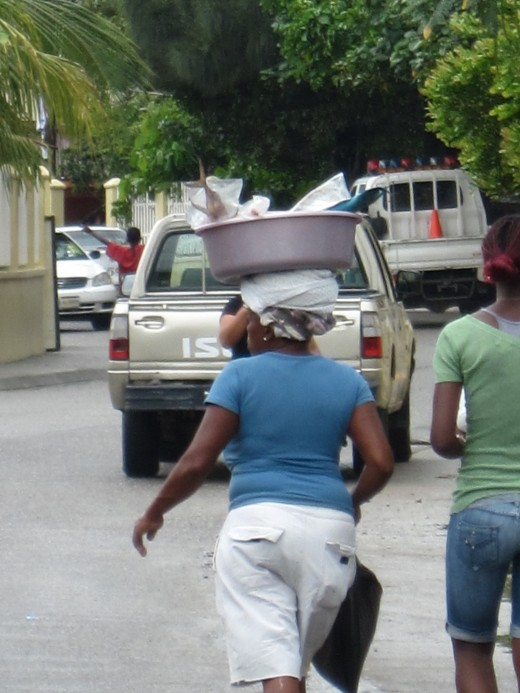 Local woman walking down main street in Coxen Hole, Honduras carrying a load of fish on her head