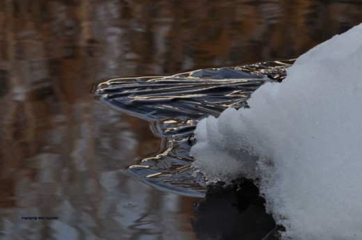 A point of ice cuts into the creek.