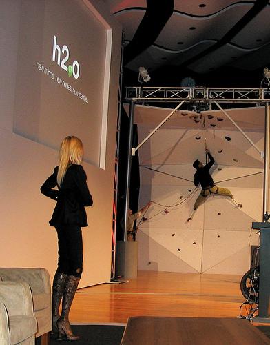 An artificially-legged person climbing a wall.
