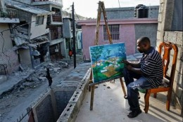 An Haitian artist sits surrounded by all the destruction around him, just so that he can sit and paint.