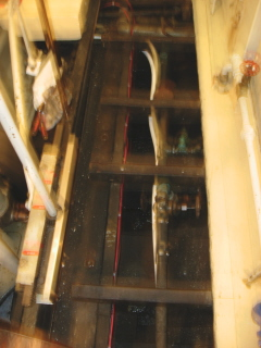 View under floorboard in engine room. Be grateful this is out of focus. It's scary in there!