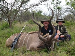 Author with a Kudu.  No shadows, rifle safely pointed away, natural background.