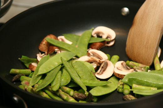 Stir frying the asparagus, mushrooms, and snow peas