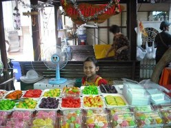 A little girl with Look Choob (Green Bean Miniature Fruit)and other Thai desserts