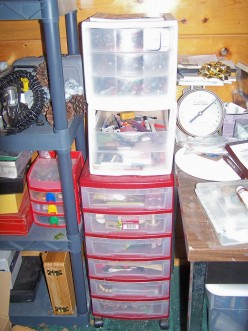A red self-contained shelf takes up little room, but holds a ton of items for jewelry making! White 3-drawer shelves on top hold art pens, pencils and markers.