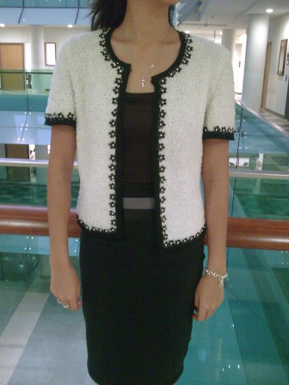 white textured cropped-sleeve jacket with black piping
