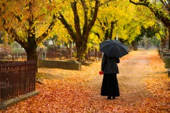 A cemetery in Autumn, a woman mourns.