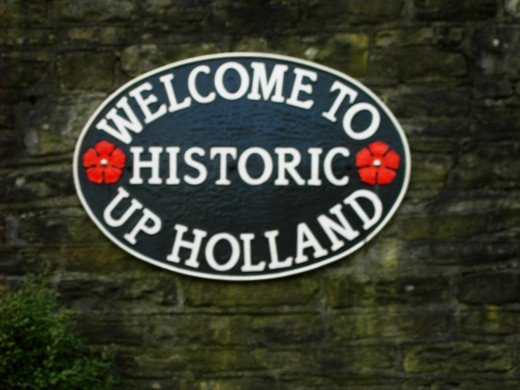 The sign was made by the skill of a village man.The red rose of Lancashire is incorporated in the design.