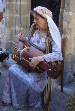 A local lady demonstrating a mediaeval musical instrument in the streets of Rochechoaurt.