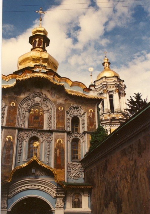The entrance to Pechersk Lavra showing the brilliantly frescoed walls and the top of the Belltower on the right.