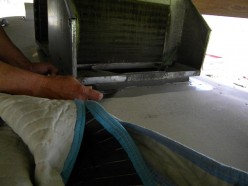 A putty knife is used to separate the old A/C gasket from the roof.