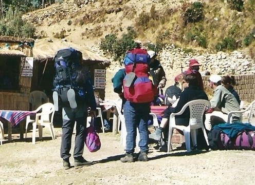 Pan American travelers cover up against Lake Titicaca's brilliant sunlight.
