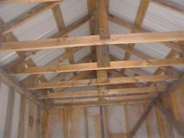 The roof trusses are home made. Purlins are running perpendicular for strength and are fastening points for the metal roofing sheets.
