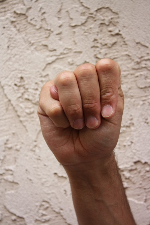Closed fist with the thumb between the pinky and ring fingers.