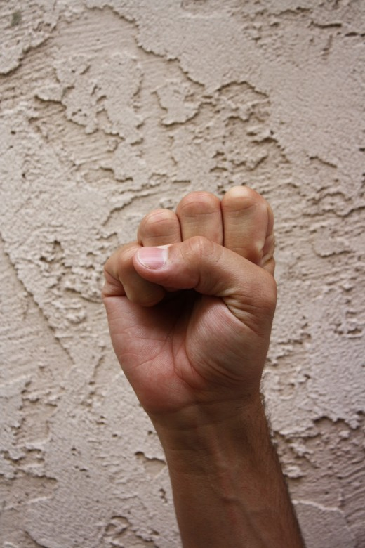 Closed fist with the thumb in front of the fingers.