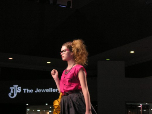 A model sashaying down the catwalk with the featured clothes and handbag.