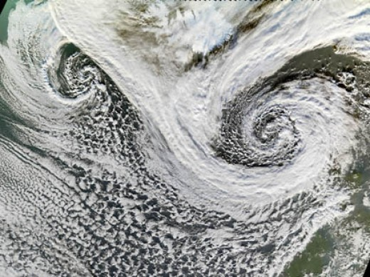 NASA Photo - Cyclones in Tandem  These two  low-pressure cyclones are winds that spiral inwards. These formed in November 2006.Although they may look like tropical storms  these types of storms can also form at mid to high latitudes.  MODIS, flying o