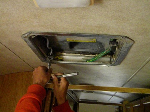 Removing retaining bolts from ceiling flange