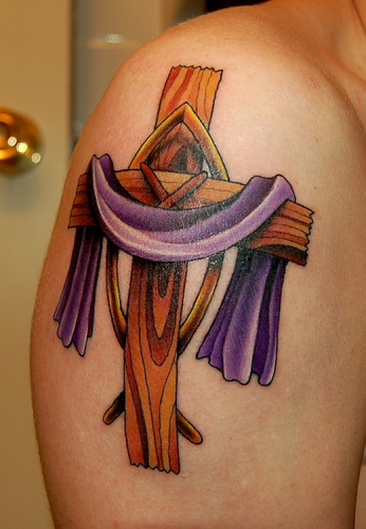 A wooden cross with the purple robe draped over is next of my tattoos of