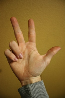 Index and middle fingers and thumb are extended.