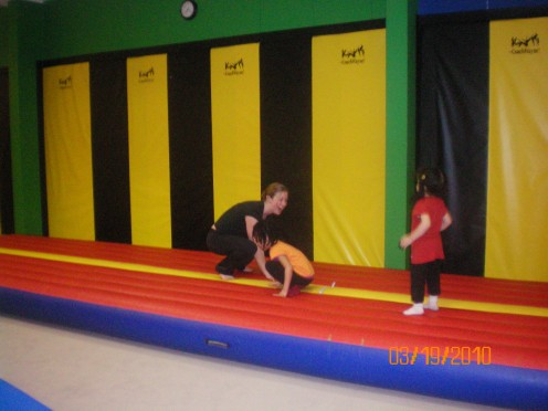 Bouncing on the bouncing pad with the trainer.