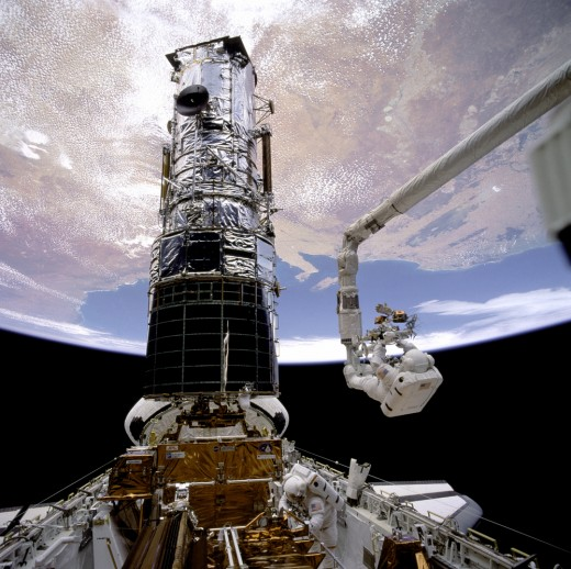 Shuttle astronauts repair the Hubble telescope. Photo courtesy of NASA.