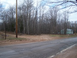 Green garage and dirt road with no sign. by Emily Glahn Eades