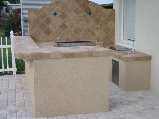 The Lazyman gas bbq grills do not come with a hood on the barbeque.  The barbecue hood has to be purchased separately.  This custom outdoor kitchen was photographed before the cast stone went on the backsplash but the Lazyman 210-40 grill can just ba