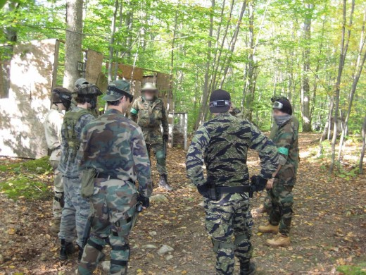 The players in this image are about to engage in close quarters combat.Everyone uses some form of eye and mouth protection.