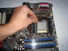 Pushing down the silver lever to secure the processor in place
