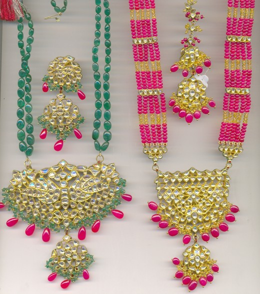 Two pieces of gold  Patrihat (Special style of Indian necklace) studded with diamond polki. Emerald and ruby beads. Earrings are also seen in the picture.