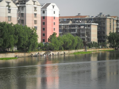 Modern buildings are a back drop to the women washing in the canal.
