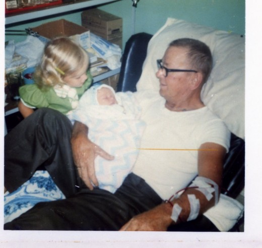 Grandpa holding me while on the kidney machine, Shannon looking on