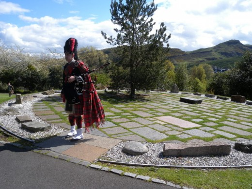 A beautifully dressed Scottish bag pipe player was playing inside the stone circle.  Each stone is a specific type of stone taken from each Scottish shire.