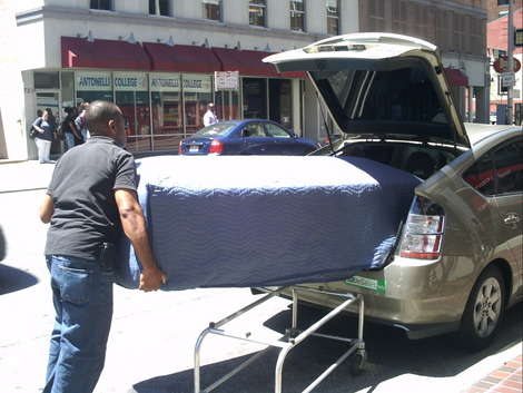 Eric Lusain, Owner of Main Street Casket Company, loads a casket into the back of his Prius for delivery. After a brief interview in his showroom, Mom snapped pictures and Son recorded a video of Eric pushing the casket down the sidewalk and loading